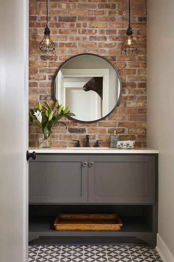 basic gray single sink bathroom vanity with brick accent wall and circle bathroom mirror