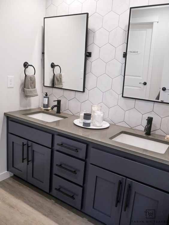 double sink bathroom vanity with dark blue cabinets and matte black handles