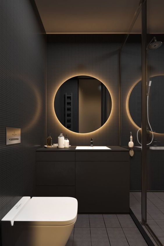 matte black modern single vanity in bathroom with black tile walls and wall mounted toilet