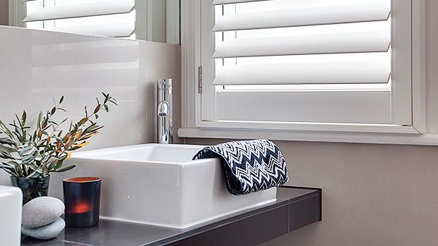 single window bathroom vanity plantation style shutters natural light