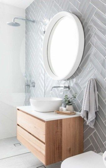 basic single vessel sink floating vanity with wood finish against chevron style gray tiles