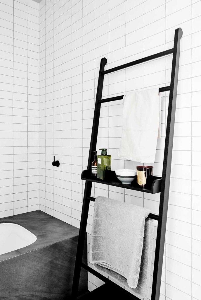 bathroom design trends of 2019 black ladder shelf next to concrete bathtub black grout tile